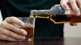 Конец-вверх: самостоятельно человек льет виски в стекле от бутылки и выпивать видеоматериал