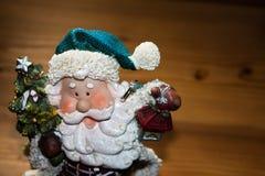 Конец-вверх Санта Клауса и кольца с бриллиантом на деревянной предпосылке Стоковые Фото