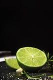 Конец-вверх свежей, зрелой, сочной половины зеленой известки на черной предпосылке Цитрусовые фрукты вполне витаминов скопируйте  Стоковое Изображение RF
