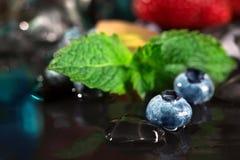 Конец-вверх свежей и яркой голубики с кубами мяты и льда Здоровые, сочные и яркие синие ягоды на черной предпосылке Стоковые Фото