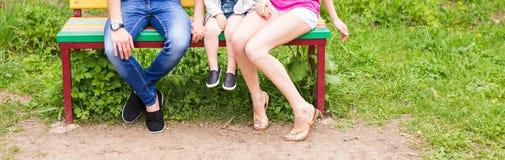 Конец-вверх семьи сидя на стенде в парке лета Стоковое Фото