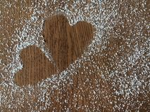 Конец-вверх 2 сердец сделанных от порошка сахара на деревянном tabl Стоковое Изображение RF