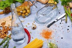 Конец-вверх серой таблицы с макаронными изделиями, бутылки, перца красного chili, грецких орехов, оливок, спаржи на свете - серой Стоковое Изображение