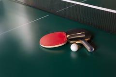 2 ракетки пингпонга и шарик на зеленой таблице сеть пингпонга стоковая фотография