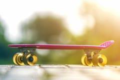 Конец-вверх скейтборда ребенка пластичного розового изолированного на мостоваой против яркой белой и зеленой запачканной предпосы стоковое изображение