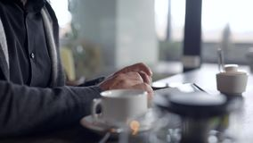 Конец-вверх снял беседовать парня онлайн на планшете в кафе, чашке чаю на таблице сток-видео