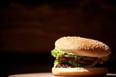 Конец-вверх снял большого, очень вкусного бургера мяса помещенного на деревянной доске Стоковые Изображения