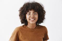 Конец-вверх снял дружелюбной симпатичной Афро-американской студентки в прозрачных стеклах и коричневом усмехаться футболки стоковая фотография