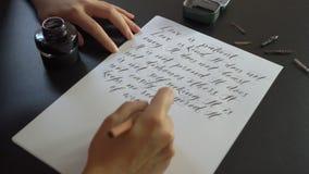 Конец вверх снял каллиграфии молодой женщины писать на бумаге используя помечать буквами метод Она пишет любовь зарока свадьбы сток-видео