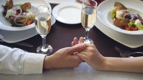 Конец-вверх снял мужской руки держа и лаская женскую руку на таблице с стеклами и плитами шампанского романтично видеоматериал