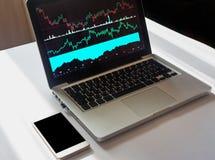 Конец вверх снял ноутбука с финансовыми данными на экране на белом d стоковое фото