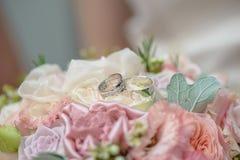 Конец-вверх снял пастельного bridal букета роз и шелк при 2 обручального кольца отдыхая на белой розе, подготавливает для свадьбы Стоковая Фотография