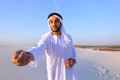 Конец-вверх снял портрета и рук молодого арабского парня в песочном d Стоковые Фото