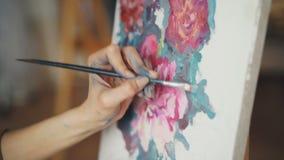 Конец-вверх снятый грязной женской руки крася красивые яркие цветки на холсте используя щетку и краски Наглядные искусства видеоматериал