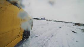 Конец-вверх снятый желтого автомобиля ралли перемещаясь в след снега видеоматериал