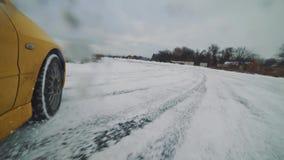 Конец-вверх снятый желтого автомобиля ралли перемещаясь в след снега сток-видео