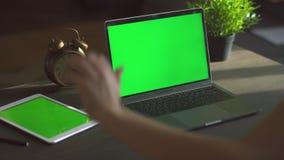 Конец-вверх снятый женских рук печатая на ноутбуке с зеленым экраном дальше Женщина используя тетрадь с зеленым дисплеем на сток-видео