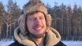 Конец-вверх снятый исследователя в клобуке и пальто наблюдая в камеру joyfully и smilingly на предпосылке леса зимы видеоматериал