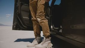Конец-вверх снятый мужских ног нося крутой выходить ботинок пустыни автомобиля минифургона в квартирах пустыни озера соли в Bonne сток-видео
