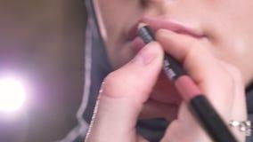 Конец-вверх снятый процесса делать макияж и установки розовой губной помады на молодую мусульманскую девушку в hijab на черной пр видеоматериал