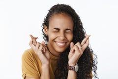 Конец-вверх снятый счастливой возбужденной и оптимистической молодой Афро-американской женщины делая желание с улыбкой и закрытым стоковые фотографии rf