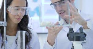 Конец-вверх снятый 2 ученых медицинского исследования смотря мышь лаборатории в стеклянной клетке Лаборатория яркая и сток-видео