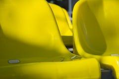 Конец-вверх снял множество желтых пластичных мест на стадионе Стоковое Изображение RF