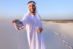Конец-вверх снял портрета и рук молодого арабского парня в песочном d Стоковые Изображения