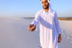 Конец-вверх снял портрета и рук молодого арабского парня в песочном d Стоковое Изображение