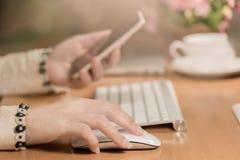 Конец-вверх современных рук бизнес-леди щелкает мышь и использует умный телефон стоковая фотография