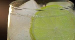 Конец-вверх соды освежающего напитка с пузырями взаимодействуя с льдом и известкой акции видеоматериалы