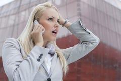 Конец-вверх сотрясенной коммерсантки связывая на сотовом телефоне против офисного здания Стоковая Фотография RF