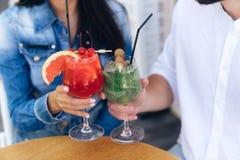 Конец-вверх стекел с пить в руках людей и женщин, коктеиля ягоды и mahito, стекел clink Питье, люди стоковые изображения