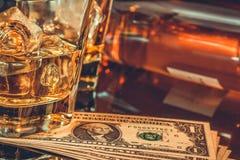 Конец-вверх стекел вискиа около бутылки и долларов на черной таблице Западный стиль темы Стоковые Изображения RF