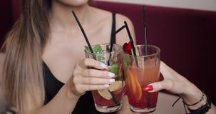 Конец-вверх 2 стекла clink друга очарования женских со свежим коктейлем и выпивать совместно сток-видео