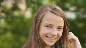 Конец-вверх стороны подростка девушки с оконфуженными веснушками и смешным представлять и играть с его волосами Стоковая Фотография RF