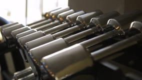 Конец-вверх строка новых стальных гантелей на шкафе спорт сток-видео