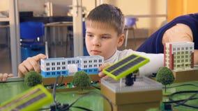 Конец-вверх Студенты начальной школы делая проект альтернативной энергии исследования на прототипе города сток-видео