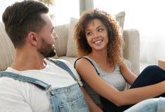 Конец-вверх счастливой пожененной пары сидя в новой квартире Стоковые Изображения RF