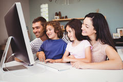 Конец-вверх счастливой семьи смотря в компьютере Стоковые Изображения RF