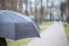 Конец-вверх темного зонтика во время дождя Стоковые Изображения