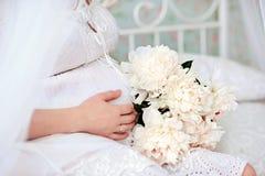 Конец-вверх торса молодой беременной модели сидит с белыми пионами в руках будущая мама Здоровая концепция материнства стоковая фотография rf