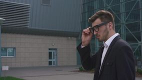 Конец-вверх уверенно красивого элегантного бизнесмена кладя на стекла пока ждущ его полет сток-видео
