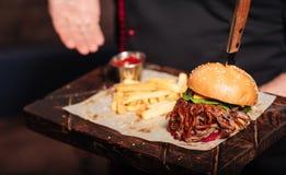Конец вверх укомплектовывает личным составом руки держа ресторан burgerin Стоковые Изображения RF