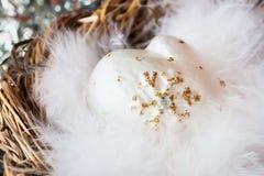 Конец-вверх украшения рождества от белых декоративных mittens целлулоида с пушистыми пер птицы в гнезде Стоковое Изображение RF