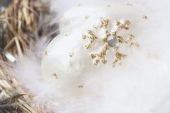 Конец-вверх украшения рождества от белых декоративных mittens целлулоида с пушистыми пер птицы в гнезде Стоковая Фотография