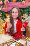 Конец вверх усмехаясь девушки нося красный костюм santa и держа шарик рождества 2 в одной руке и 2 подарках в ей Стоковые Изображения