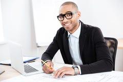 Конец-вверх усмехаясь умного бизнесмена работая с компьютером Стоковые Изображения