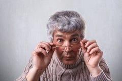 Конец-вверх удивленного взрослого при серые волосы и морщинки нося стекла Старший человек касаясь его eyeglasses смотря с широко стоковая фотография
