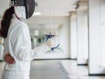 Конец-вверх фехтовальщика в белом ограждая костюме и держать шпагу o стоковая фотография